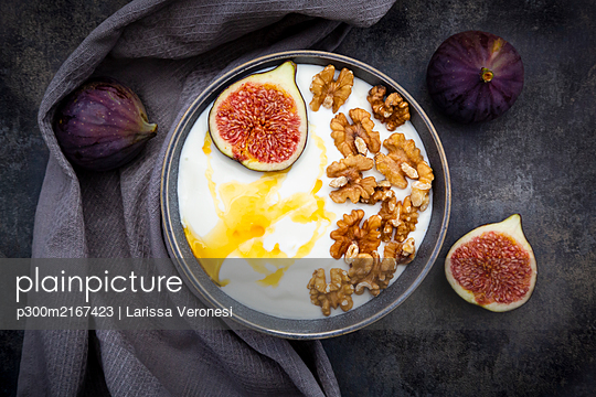 Bowl of Greek yogurt with honey, walnuts and sliced fig - p300m2167423 by Larissa Veronesi