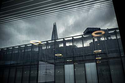 View of the City of London skyline form inside a nearby building showing the Shard building obscured by internal reflections and rain on the glass window. - p1057m2089726 by Stephen Shepherd