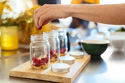 Close-up of woman in kitchen putting raspberry into jar - p300m1588173 von Bonninstudio