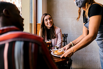 Waitress serving food to smiling young couple at cafe during COVID-19 - p300m2220855 by Ezequiel Giménez