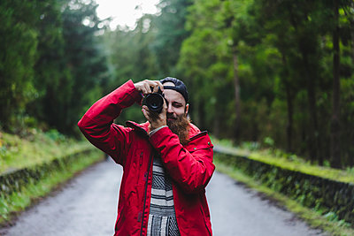 Young male tourist photographing through camera while standing on road - p300m2298824 by VITTA GALLERY