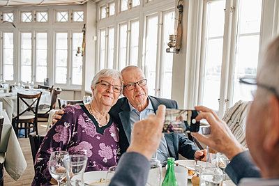 male friend clicking photograph of Senior couple in restaurant - p426m2149114 by Maskot