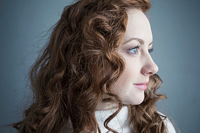 Portrait pensive Caucasian woman with curly red hair looking away - p1192m1213139 by Hero Images
