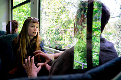 Junges Paar im Gespräch in der Bahn - Reflexion - p1212m1138821 von harry + lidy