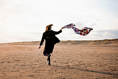 Woman running with beach blanket - p429m2075113 by Tom Dunkley
