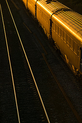 Rail lines lit by the late evening light as it reflects from the track - p1057m1475313 by Stephen Shepherd