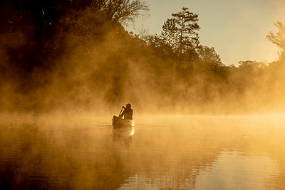 Sunrise canoe ride on foggy river. - p1166m2269649 by Cavan Images