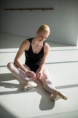 Ballerina tying her ballet shoes - p1315m1230734 by Wavebreak