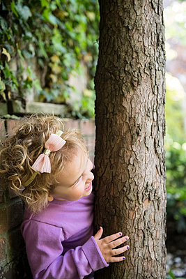 Caucasian girl hiding behind tree trunk - p555m1531566 by JGI/Jamie Grill