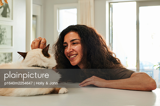 Woman stroking her cat, portrait - p1640m2254647 by Holly & John
