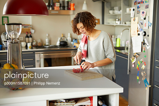 Mature woman cutting tomato in kitchen - p300m1587091 von Philipp Nemenz