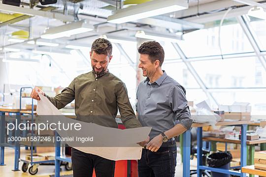 Two smiling men looking at plan in factory - p300m1587246 von Daniel Ingold