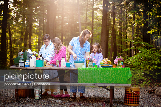 Three generations of Caucasian women cooking at picnic table - p555m1409460 by Shestock