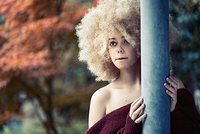 Young woman with curly lions mane - p1569m2195804 by Moritz Metzger