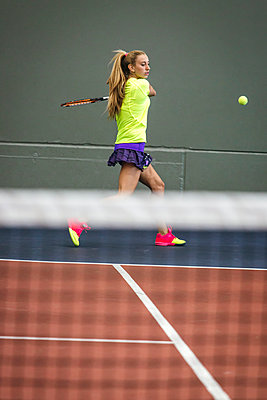 Young woman playing tennis in an indoor tennis center - p300m1059064f by Marco Govel