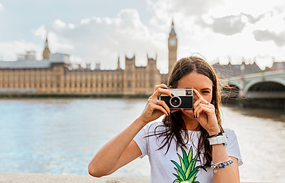 UK, London, beautiful woman taking a picture near Westminster Bridge - p300m1505468 by Marco Govel
