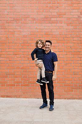 Portrait of smiling father carrying son at brick wall - p300m2080960 von Mauro Grigollo