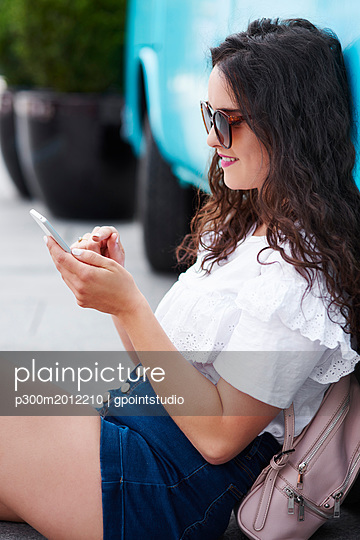 Smiling young woman sitting outdoors using cell phone - p300m2012210 von gpointstudio