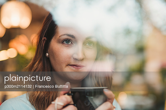 Young woman in a cafe drinking coffee behind windowpane - p300m2114132 von Francesco Buttitta