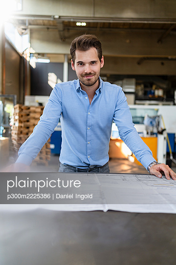 Smiling man leaning on table while working  at factory - p300m2225386 by Daniel Ingold