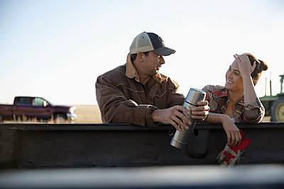 Farmer couple drinking coffee, taking a break on farm - p1192m2040123 by Hero Images