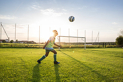 Young football player heading the ball on football ground at sunset - p300m1581350 by Fotoagentur WESTEND61