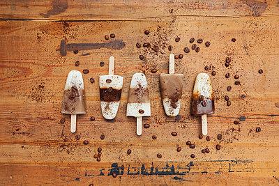homemade Espresso Macchiato, Latte Macchiato and Cappuccino ice lollies with coffee beans on wooden background - p300m2023486 von Gaby Wojciech
