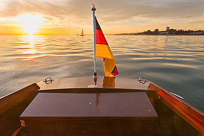 Germany, Baden-Wuerttemberg, Lake Constance, motorboat, German flag at sunset - p300m2082996 by Holger Spiering