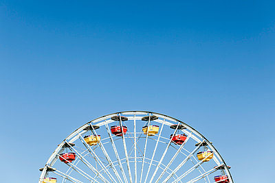 Low angle view of Ferris wheel against clear blue sky - p301m1029336f by Patrick Strattner