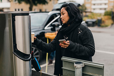 Mid adult woman with smart phone at electric car charging station - p426m2195293 by Maskot