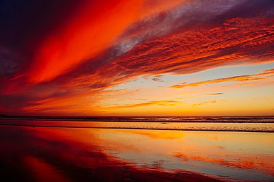 Deserted beach under dramatic orange sky at sunset, San Diego, California, USA - p924m1094744f by Pete Saloutos