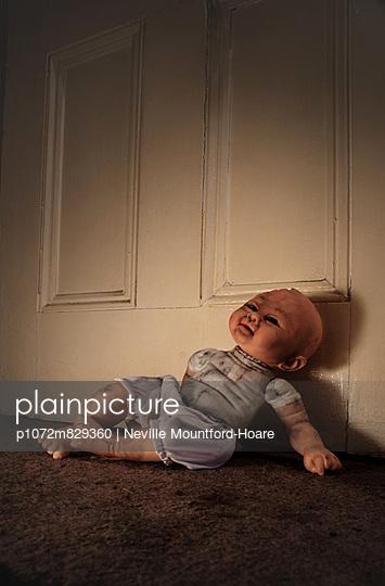 Broken doll propped against door - p1072m829360 by Neville Mountford-Hoare