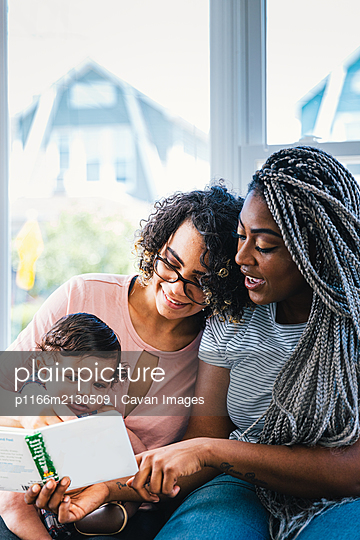 Lesbian mothers showing picture book to cute son at home - p1166m2130509 by Cavan Images