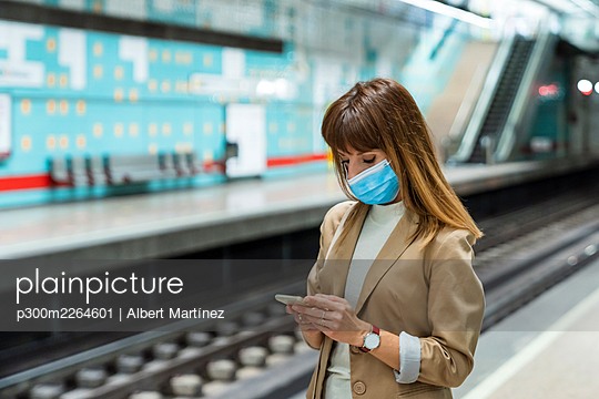 Woman with protective face mask using mobile phone while standing at subway station during pandemic - p300m2264601 by Albert Martínez