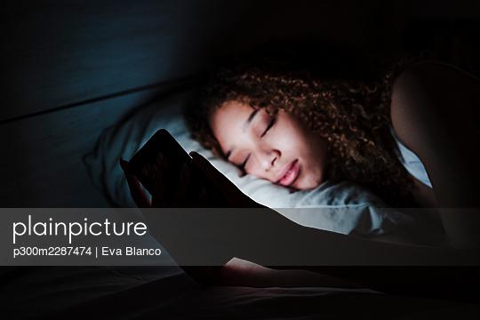 beautiful smiling hispanic using mobile phone on bed, night time, Madrid, Spain - p300m2287474 von Eva Blanco