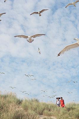 Two girls in the dunes with birds - p1323m2015150 von Sarah Toure