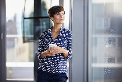 Smiling businesswoman in office looking out of window - p300m2081135 by Rainer Berg