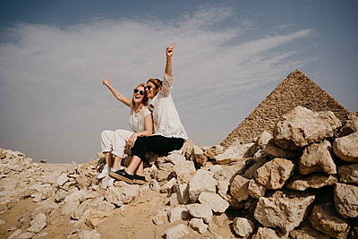 Egypt, Cairo, Two female tourists sitting together on rocks with Great Pyramid of Giza in background - p300m2266714 by letizia haessig photography