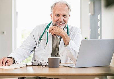 Smiling male medical professional at desk - p300m2293974 by Uwe Umstätter