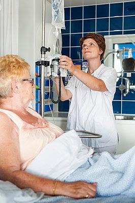 Nurse adjusting patient's intravenous drip - p429m1197999 by Arno Masse