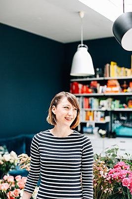 Portrait of female student florist at flower arranging workshop - p429m1418099 by Alys Tomlinson