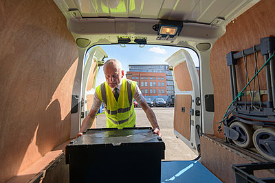 Senior delivery driver loading all electric van - p429m1578465 by Monty Rakusen