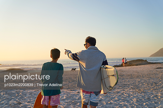 Father and son with surfboards on sunny beach - p1023m2200839 by Trevor Adeline
