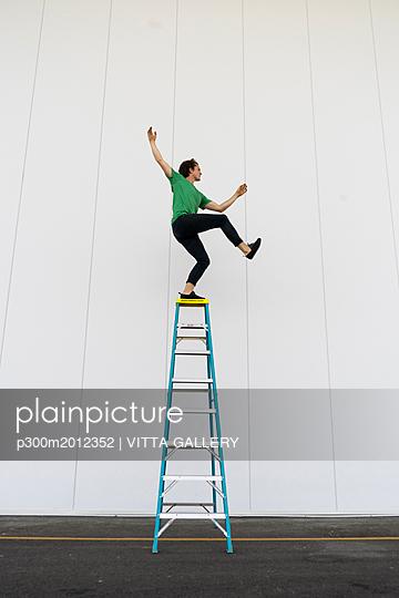 Acrobat balancing on ladder - p300m2012352 von VITTA GALLERY