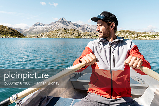 Young smiling man in a rowing boat, Lake Suretta, Graubuenden, Switzerland - p300m2167180 by Hannah Bichay