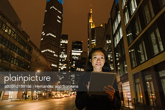 Portrait of a young woman in the city at night, Frankfurt, Germany - p300m2188156 by Hernandez and Sorokina