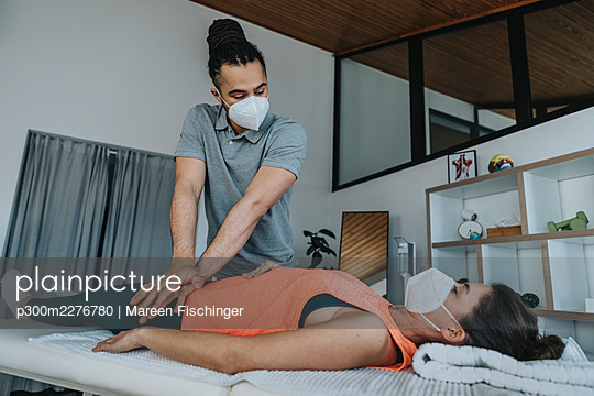 Male physiotherapist in protective face mask checking leg of female patient in medical practice during COVID-19 - p300m2276780 by Mareen Fischinger