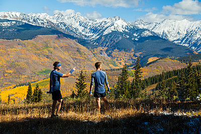 Men on trail run look at Gore Range mountains from Vail, Colorado - p1166m2137915 by Cavan Images