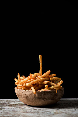 French fries in a earthenware bowl, on a table - p1423m2149797 by JUAN MOYANO