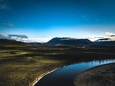 Flussverlauf mit weiter Landschaft und Berge im Hintergrund - p1455m2203771 von Ingmar Wein